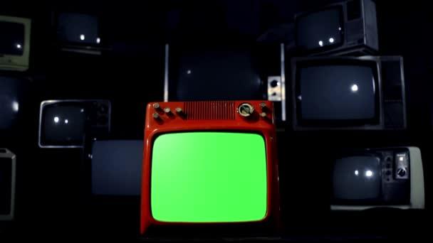 Régi piros Tv zöld képernyő közepén sok TV-vel felszerelt kék acél hang. Kész arra, hogy cserélje ki a zöld képernyő felvétel vagy képet szeretne. Meg tudod csinálni a beírása (Chroma Key) hatása az Adobe After Effects vagy más video szerkesztés szoftver.