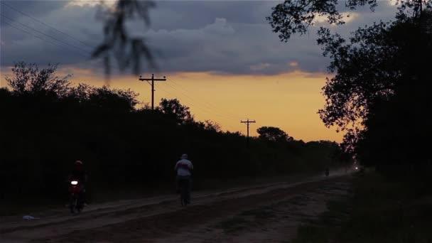 Cyklistický jezdec na venkovské silnici při západu slunce.