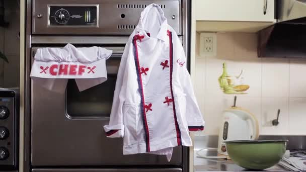 Woman Picking Up A Chef Uniform In The Kitchen. Zoom In.