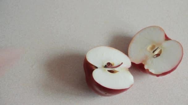 Mužské samostatné broušené červené jablko na dvě části na stole. Mužské ruce držet červené jablko s kapičkami vody. Veganská připravit ovoce k obědu. Pohled shora. Rozložení bytu