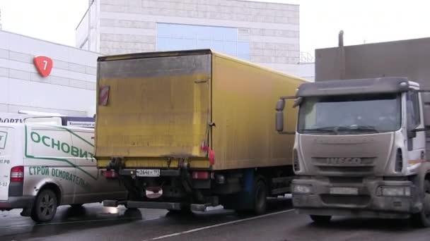 moskau, russland - 26. januar 2018: ein frachtwagen fährt in den ausstellungspavillon. Ein Wachmann mit Walkie-Talkie in leuchtend grüner Weste. expocentre auf krasnaya presnya.