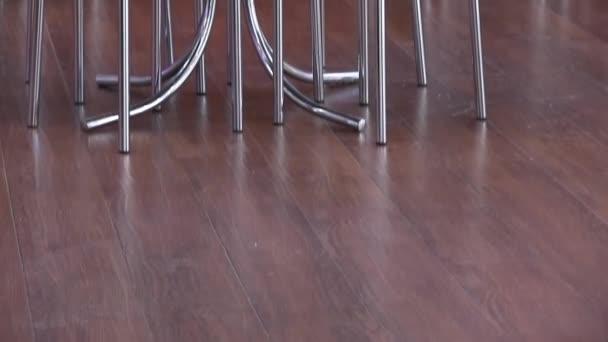 Panoramablick auf Boden und Möbel in der Mensa-Snackbar. Laminat und Stahl Stühle und Tisch mit Pfeffer und Salz in Gläsern. Servietten im Ständer. rote Wand mit grünem Streifen. Restaurant im modernen Stil