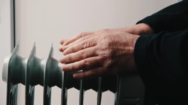 Ein älterer Herr wärmt seine Hände über einer Elektroheizung. In der Nebensaison verzögert sich die Zentralheizung, so dass die Menschen zusätzliche Heizungen kaufen müssen, um die Häuser trotz höherer Stromrechnungen warm zu halten