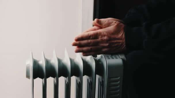 An elderly senior man warms his hands over an electric heater
