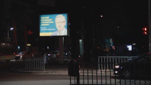 DNIPRO, UKRAINE - FEBRUARY 11, 2019: Illuminated billboard. Advertising election campaign of presidential candidate Anatoly Gritsenko. Evening street. Crosswalk. People cross the road. Traffic light