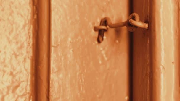 Am Abend öffnet die Hand eines Mannes eine Holztür in einem Haus an einem Haken verschlossen. Glühlampen. Die Holztür ist lackiert Beige. Dunkle Tür. Primitive Türschloss