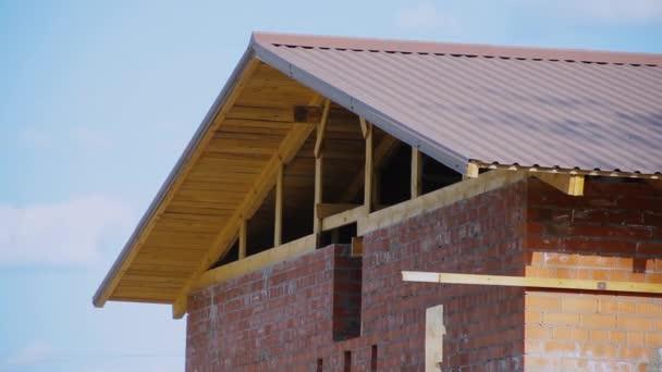 Dům je ve výstavbě proti modré obloze. Cihlové červené