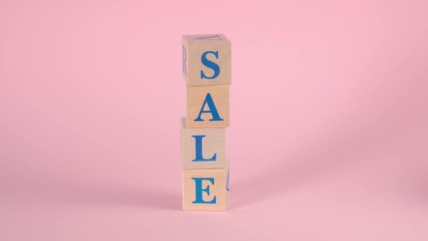 Koncept velkého prodeje na černý pátek nebo velkou slevu. Miniaturní supermarket vozík s dárkovými krabicemi uvnitř vyjíždí a zničit slova PRODEJ z dřevěných kostek. Online nakupování v obchodě