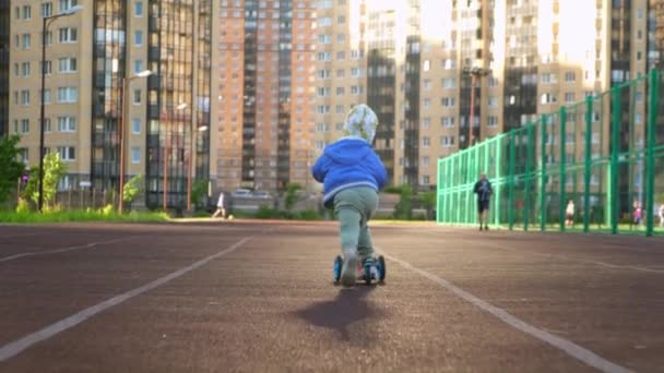 Slow motion video happy smiling caucasian little boy rides children scooter, looks back at camera along sports road for running in Sunny summer weather against background of tall residential buildings