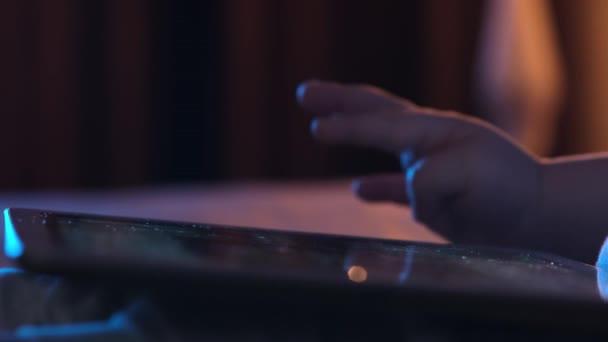 Nahaufnahme eines kleinen Jungen, der ein Tablet mit Touchscreen hält. Kind scrollt Bildschirm mit dem Finger auf der Suche nach Bildern oder liest Nachrichtenfeed im Internet.