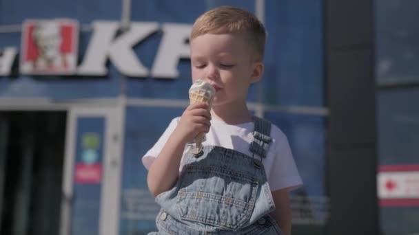 Petrohrad, Rusko, srpen 2020: Roztomilý malý blonďatý chlapec jí smetanový kornout ve vaflovacím poháru na ulici v slunečném letním počasí na pozadí slavného fast foodu KFC.