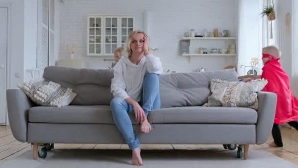 Ruhige, ausgeglichene Mutter von zwei Kindern sitzt auf dem Sofa, nicht nervös und nicht schreiend, Kinder rennen um sie herum, schreien und spielen, blondes Mädchen und Junge in rotem Heldenmantel und Schwert in der Hand.