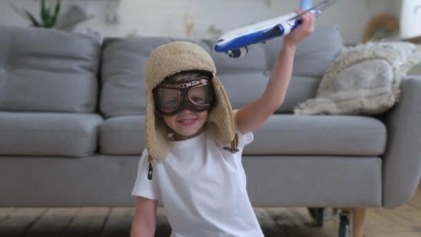Junge träumt davon, fliegen zu lernen. Glücklicher kleiner Junge, der mit weißem Passagierflugzeug mit Brille und Pilotenhut spielt und tagsüber auf dem Boden einer Wohnung sitzt. Konzept von Reisen und Abenteuer.