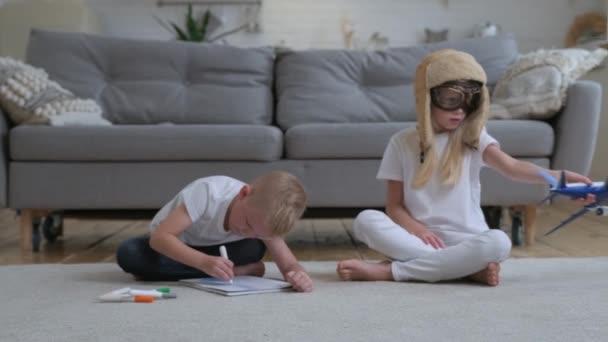 Glücklich zusammen spielen Bruder und Schwester im Zimmer, auf dem Boden sitzend. Bruder zeichnet Bild mit farbigen Filzstiften, Schwester spielt mit Spielzeug-Passagierflugzeug und träumt davon, Luftschiffpilot zu werden.