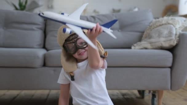 Glücklicher kleiner Junge, der mit weißem Passagierflugzeug mit Brille und Pilotenhut spielt und tagsüber auf dem Boden einer Wohnung sitzt. Junge träumt davon, fliegen zu lernen. Konzept von Reisen und Abenteuer.