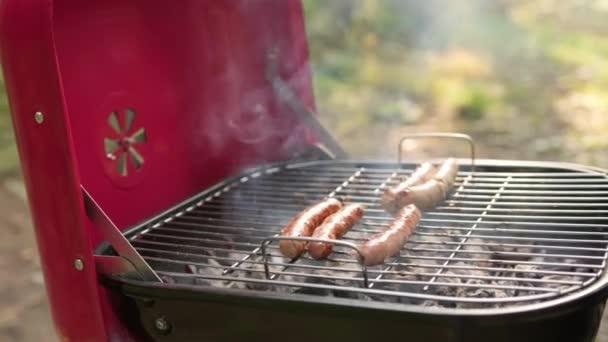 Grilované klobásy s kůrkou na grilu. Člověk na pikniku připravuje šťavnaté klobásy na žhavém uhlí. Šéfkuchař sbírá hotové šťavnaté klobásy se zlatou kůrkou s kuřecím masem, vepřovým masem a hovězím masem, se železnými kleštěmi.