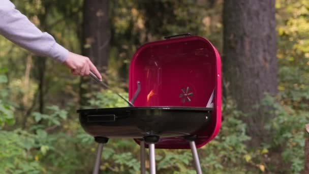 Připravte gril na vaření masa a zeleniny na dovolené. Velký plamen s ohněm hořícím na rožni. Horké uhlí hoří v pánvi a kuchař míchá žhavé uhlí železnou vidlicí..