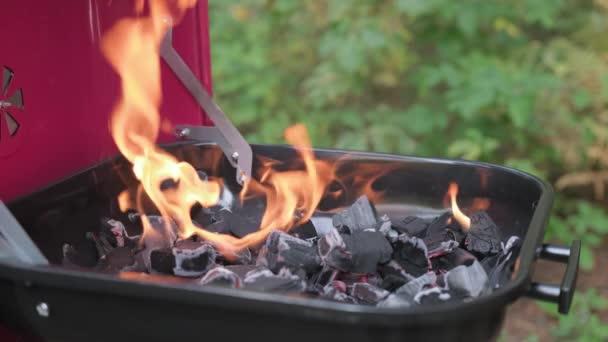 Zpomalit video velký plamen s ohněm hořící v grilu. Horké uhlí hoří v pánvi a kuchař míchá žhavé uhlí železnou vidličkou. Připravit gril na vaření masa a zeleniny na dovolené.