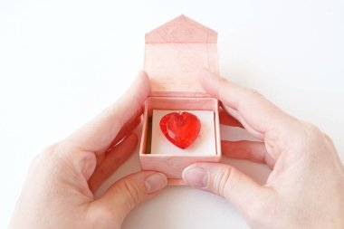 hand holds a pendant in the form of a red heart of a gemstone on a chain on white background, love and wedding concept