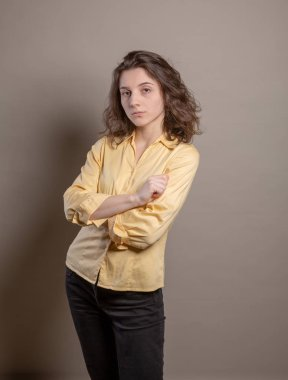 Woman in yellow shirt in studio on grey background. Spokesperson series concept.
