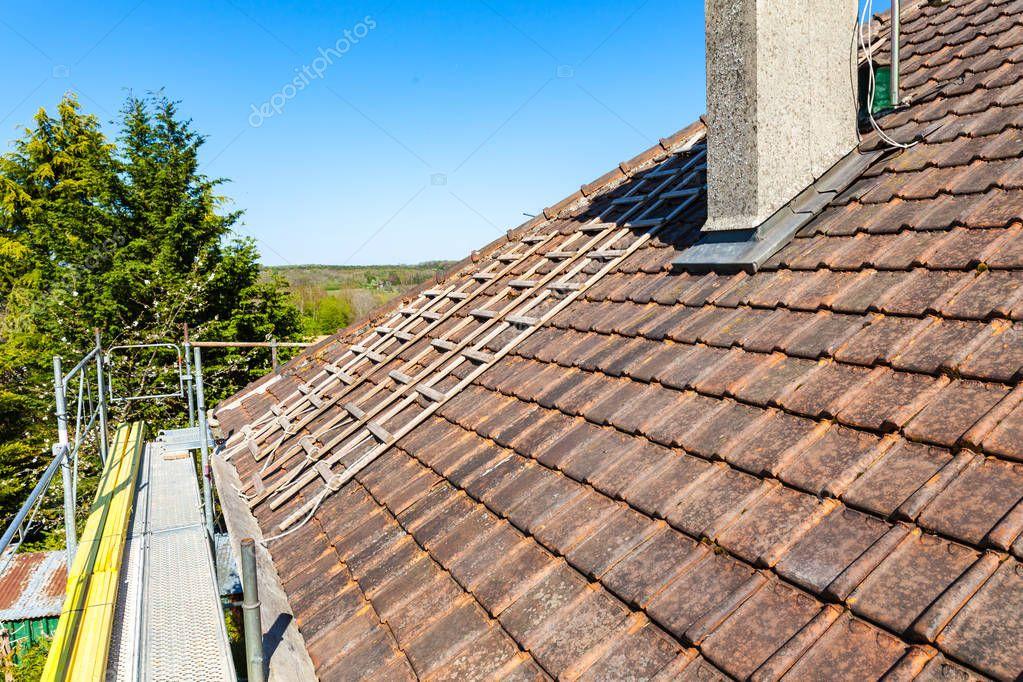 renovation of brick tiled roof on blue sky background