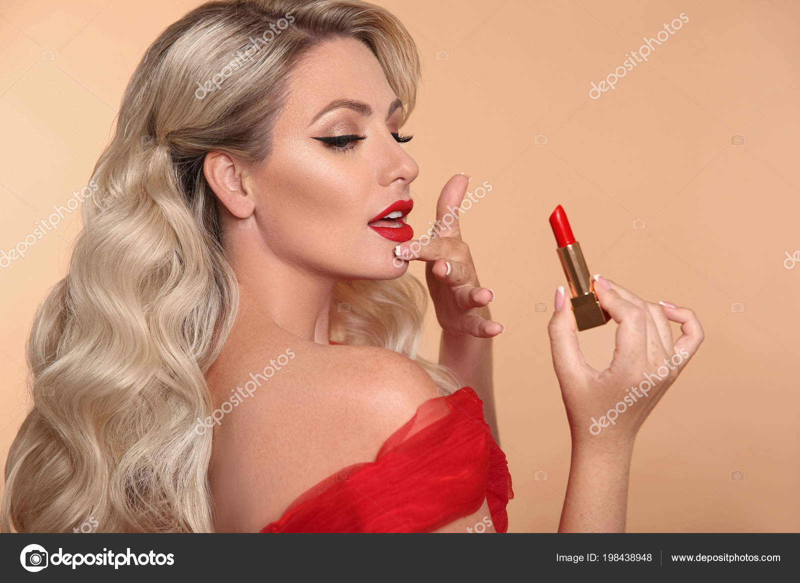 Beauty makeup. Fashion glamour portrait of sexy blonde woman with red lips and long wavy hair style holding lipstick over beige studio background.