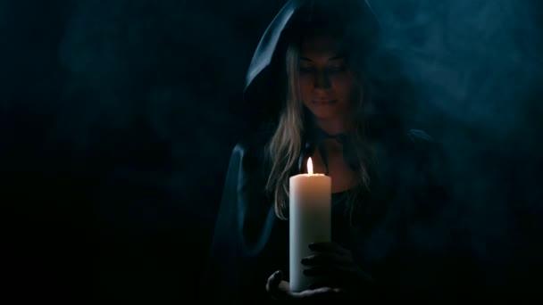 Žena v balck mys se svíčkou