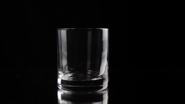 Eiswürfel, der in Zeitlupe ins leere Glas fällt. geringe Schärfentiefe