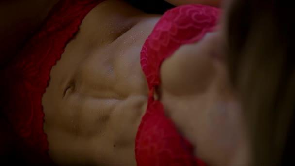 Trup vhodné mladé ženy v červeném prádle s kapkami rosy na kůži na černé