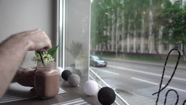Table still life at coffee shop with bouqet of spring flowers at window, cocoa with straw