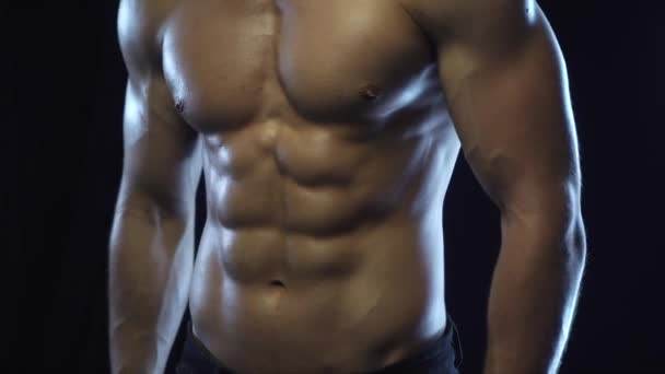 Mladý fit chlap pózuje, ukazuje břišní svaly, bezešvé smyčky, zpomalený pohyb