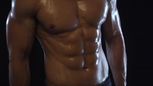 Mladý fit chlap ukazuje břišní svaly