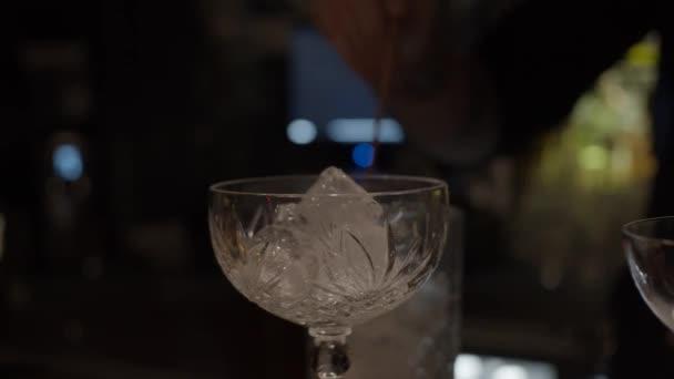 Eis im Cocktailglas, Schieberegler mit Barkeeper, der Eis im Mischglas auf dem Hintergrund mixt