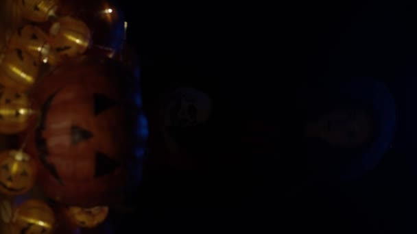 Young witch with skull and pumpkins, slow motion. Vertical video