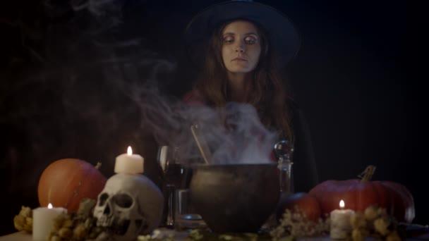 Fiatal boszorkány nézi gőzölgő üst, fókusz átmenet