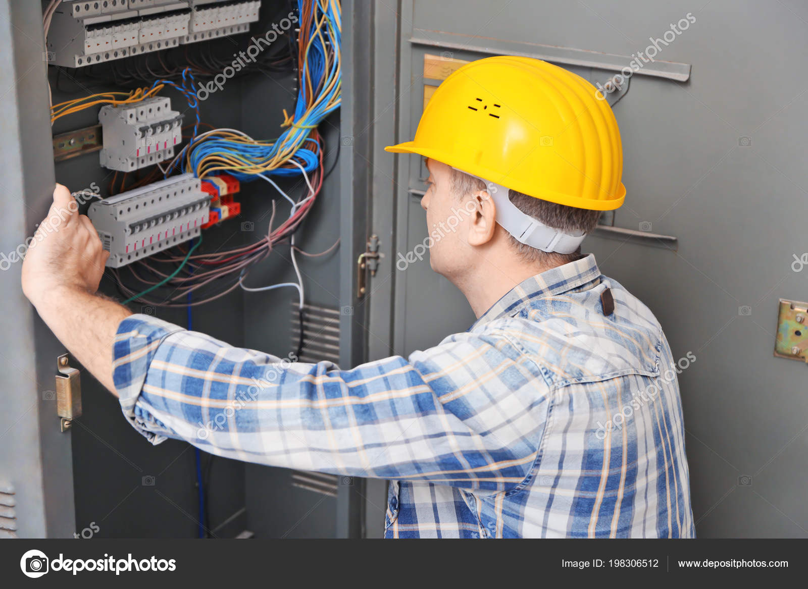 Mature Electrician Repairing Distribution Board Indoors Stock Wiring A Photo