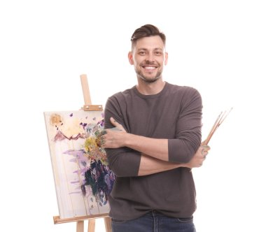 Male artist with paintbrushes near easel on white background