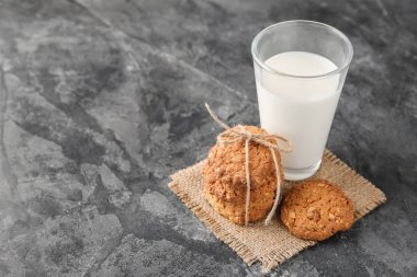 Delicious oatmeal cookies and glass of milk on grey background