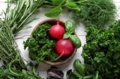 Összetétele a különböző friss fűszernövények és zöldségek, a fából készült háttér