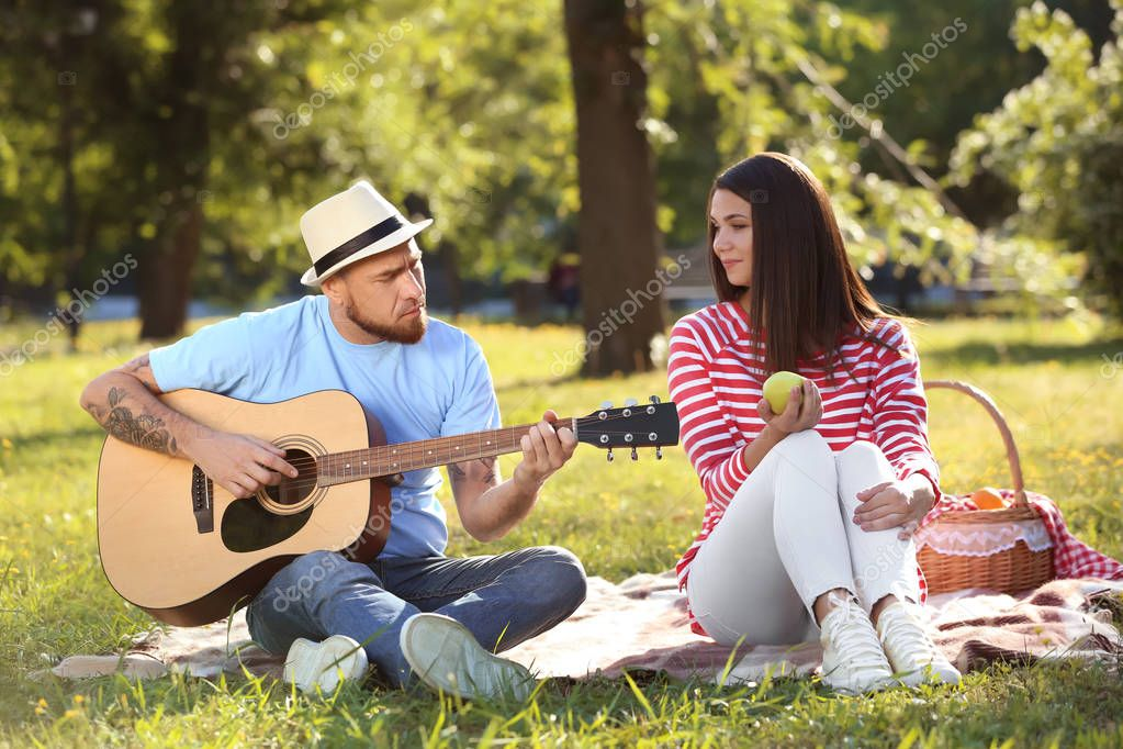 Happy couple with guitar resting on picnic in spring park