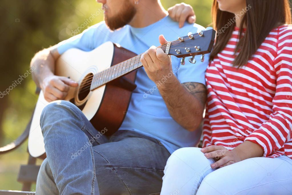 Happy couple with guitar resting in park on spring day
