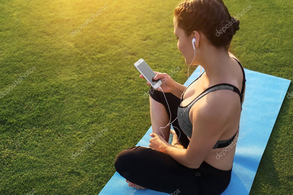 Beautiful young woman sitting on yoga mat and listening to music outdoors