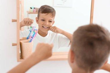 Little boy flossing teeth in bathroom