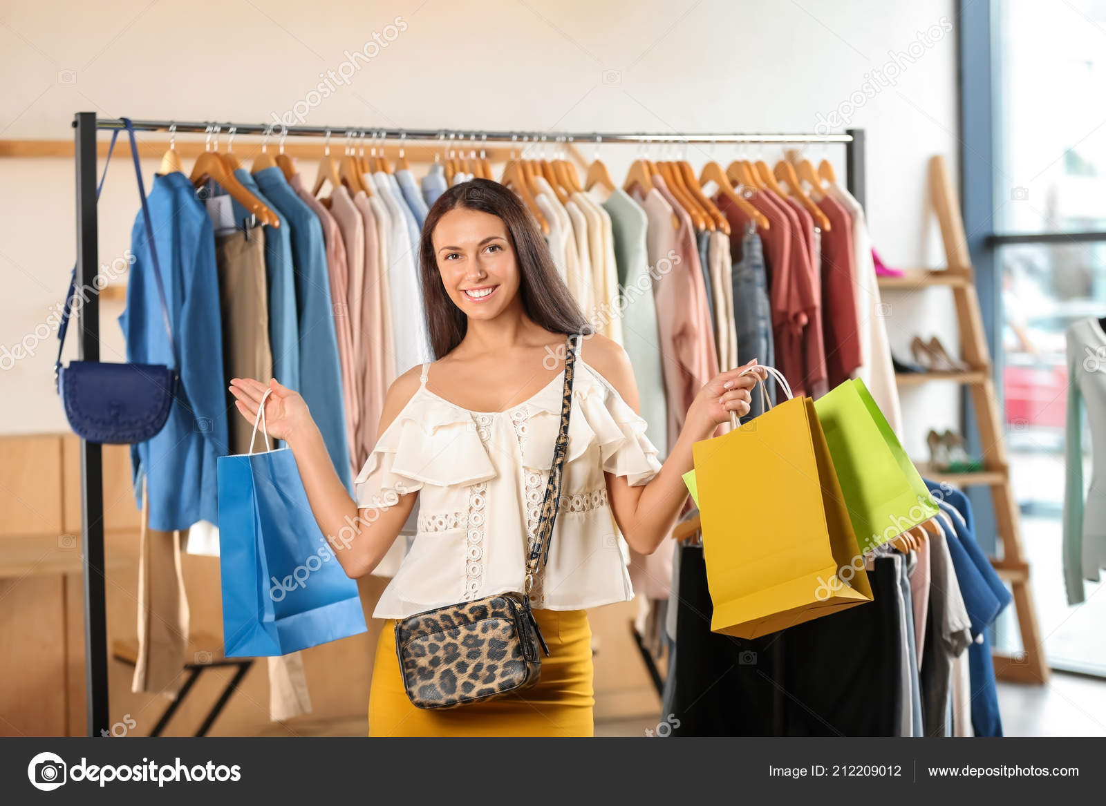 8f24aa25b2 Beautiful young woman with shopping bags in clothing store — Photo by ...