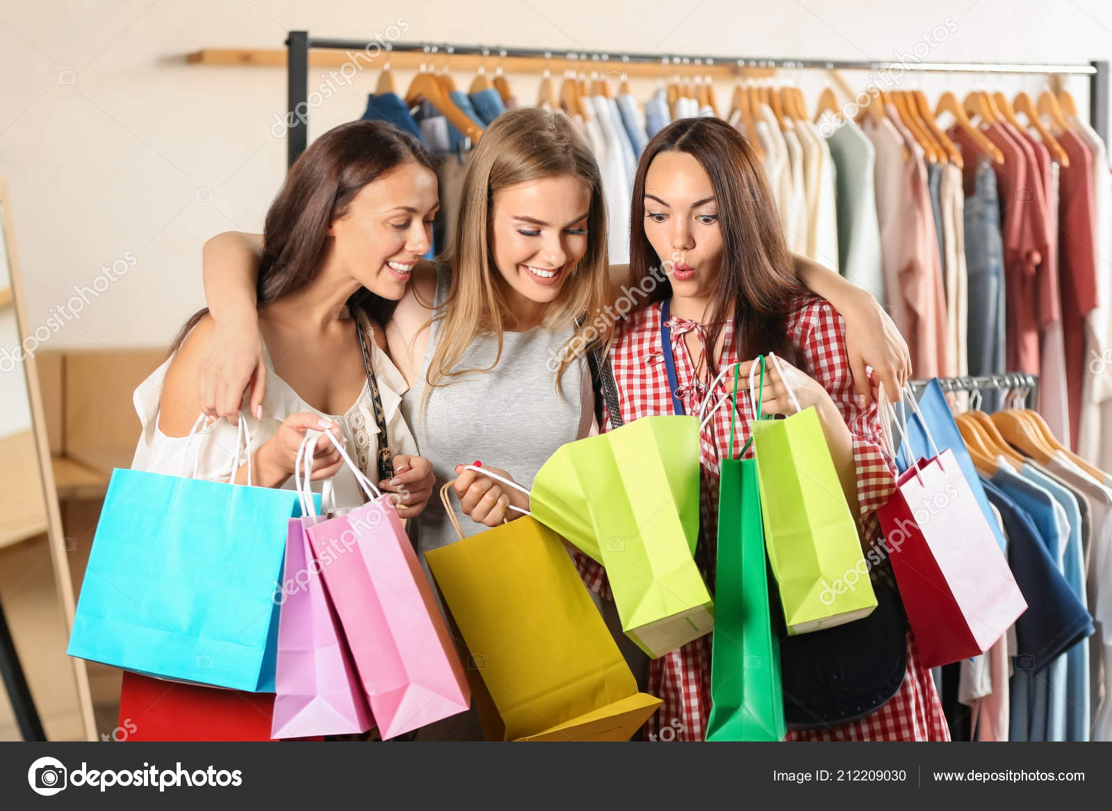 441b9ceb9a Beautiful young women with shopping bags in clothing store — Photo by ...