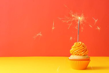 Delicious birthday cupcake with sparkler on color background