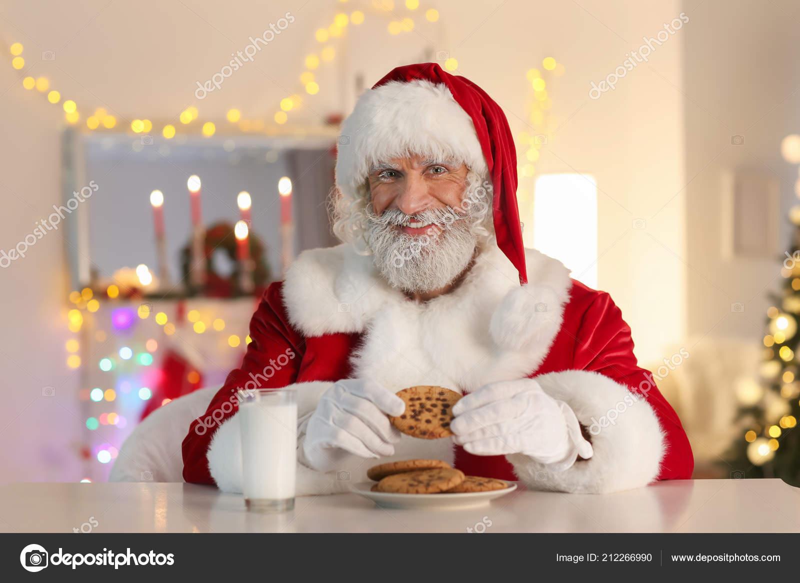 Santa Claus comiendo galletas y beber leche en la mesa en la sala decorada  para la Navidad — Foto de serezniy 8c5e56670c7