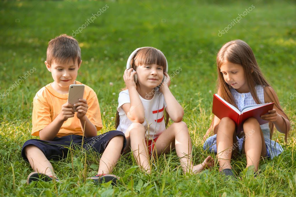 Cute little children reading book and listening to music in park on summer day