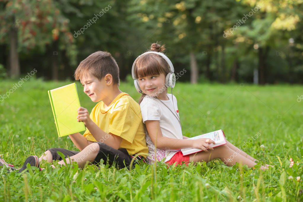 Cute little children reading books and listening to music in park on summer day