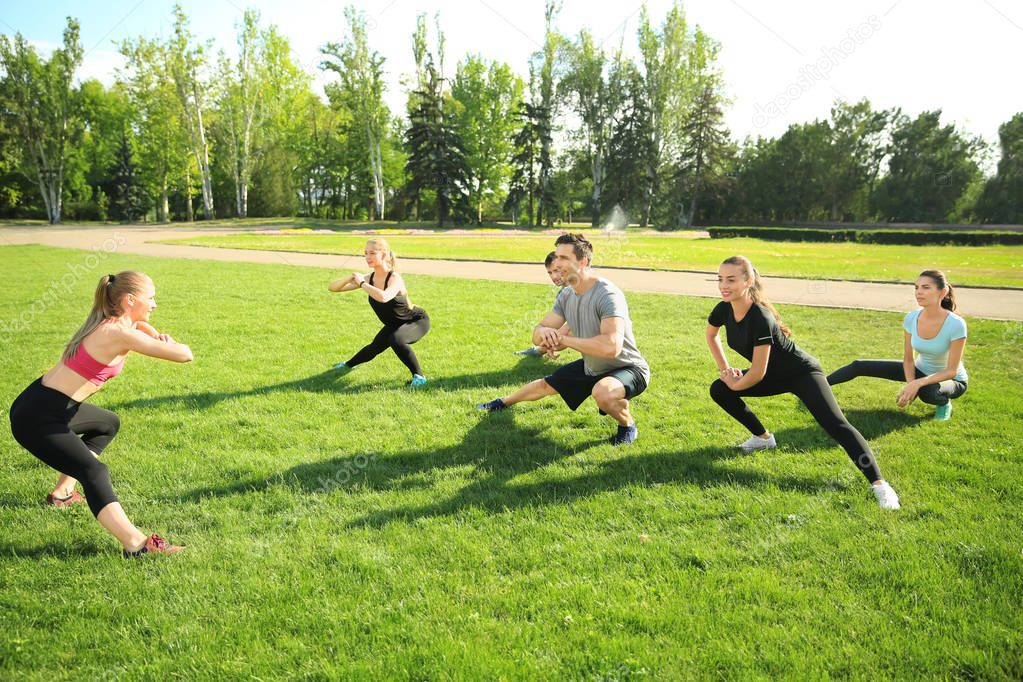 Group of sporty people training in park